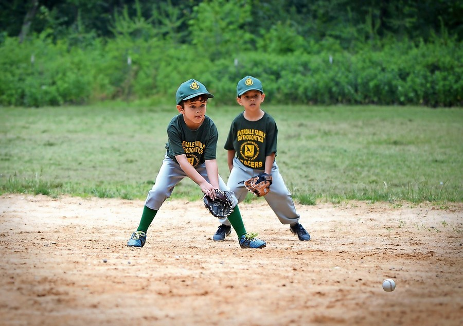 Lucas Flambury, left, and Evan Rivera of the Riverdale Family Orthodontics Bracers, make a play on a ground ball during the North Riverdale Little League Instructional League finale June 17.