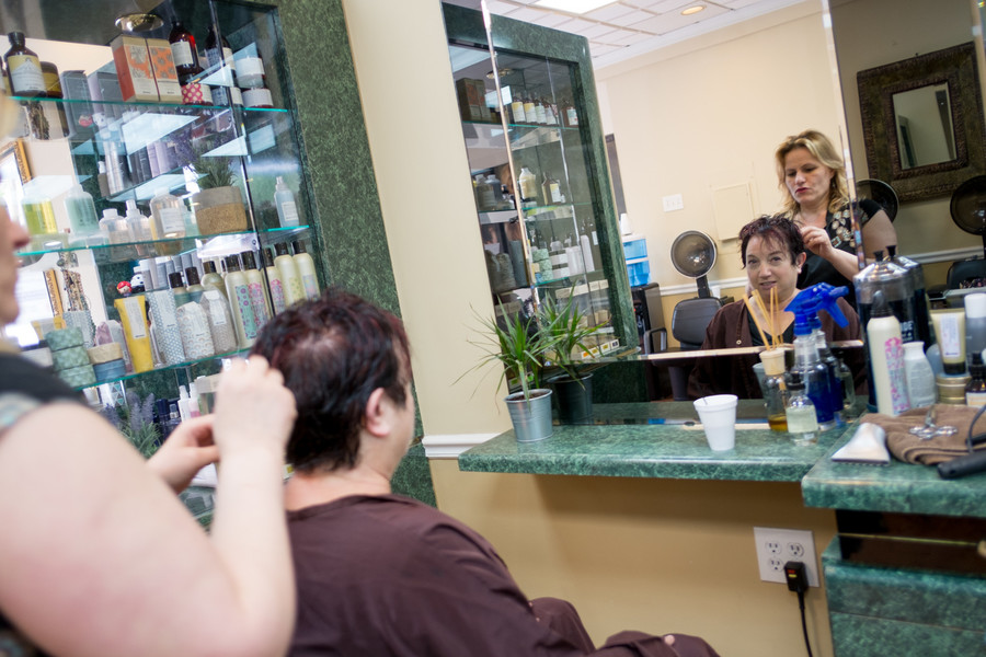 Yetta Lazri, the owner of Touch of Sun, styles a customer's hair. After an accident that claimed their old location just after the new year, Touch of Sun is making its work with fellow salon One World Unisex permanent.