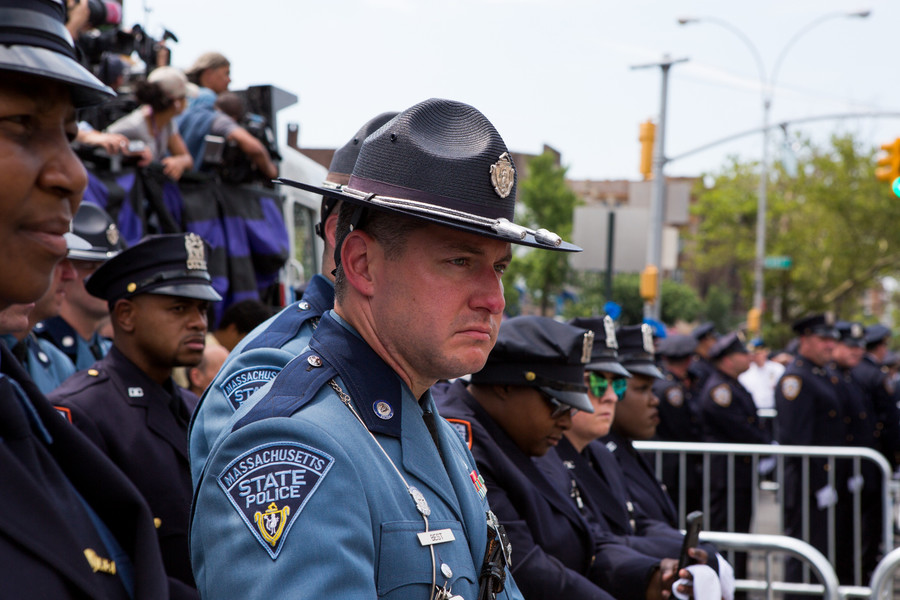 A Massachusetts State Police officer stands stolidly at attention.