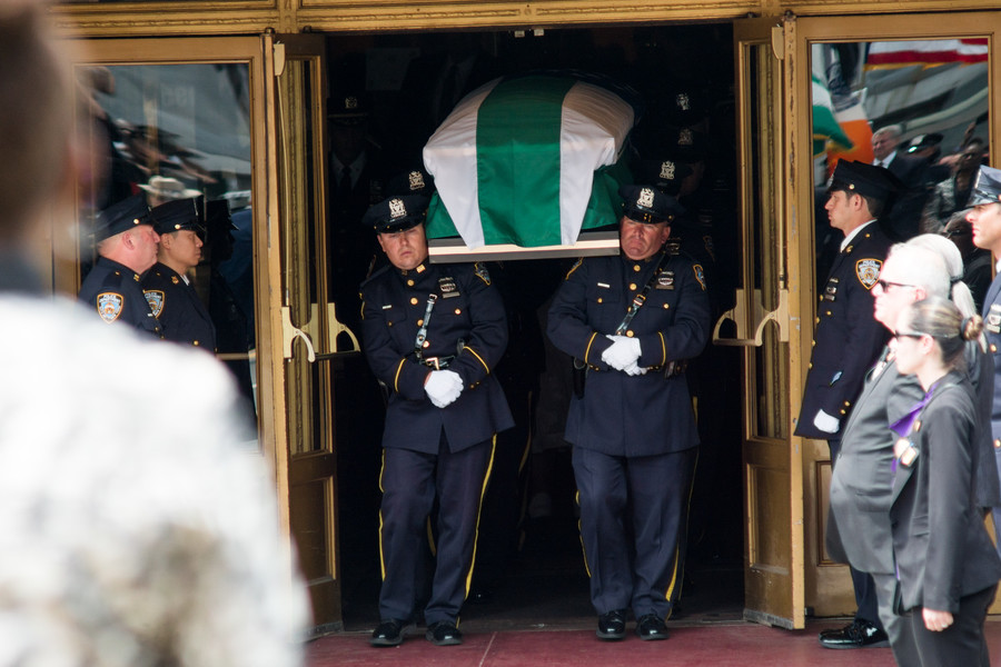 NYPD officers carry the casket of Miosotis Familia walk out of World Changers Church.