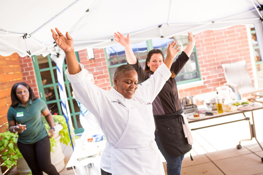 The chefs hold up their hands to show that they have finished cooking. Each made corn fritters and added her own unique twist.
