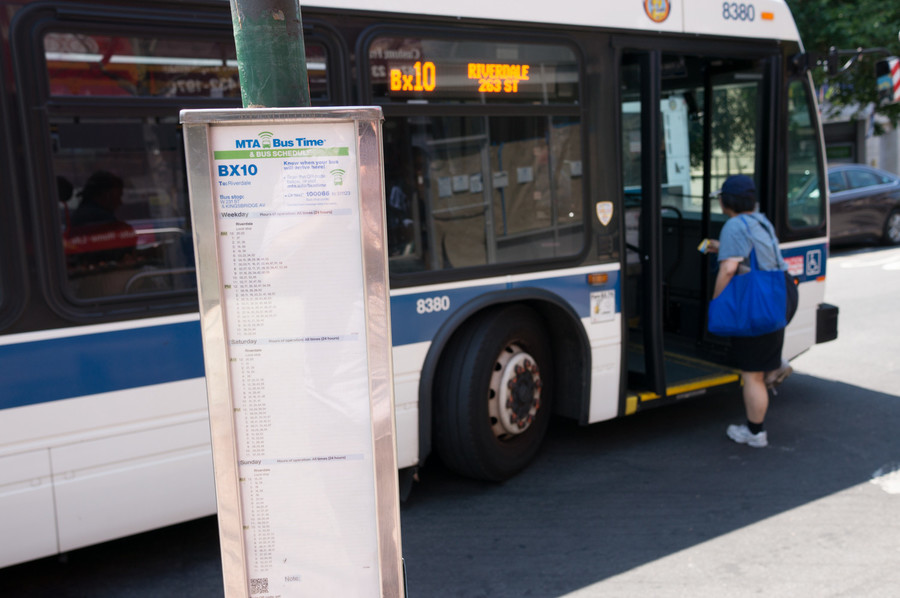 A woman boards the Bx10 just as it's leaving the stop. While the pole may indicate the availability of the Bx20, there is no posted schedule for it.