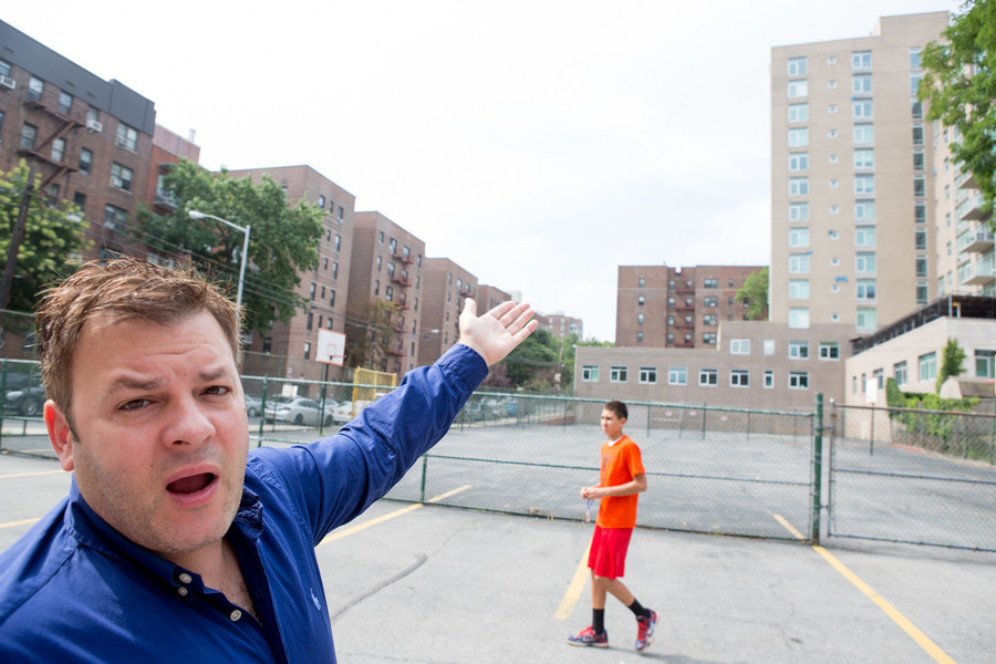 Frank Menard, a parishioner of St. Gabriel's Roman Catholic Church, shows how falling bricks from Riverstone Condominium, 3220 Arlington Ave., has forced the church to fence off part of its playground. The south side area, which was fenced off for safety reasons, has taken half of the yard away from the school.