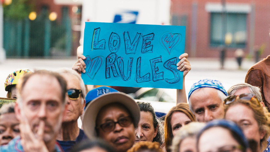 "A Riverdale resident holds up a sign that reads ""Love Rules"" at a vigil against the hateful rhetoric from various white supremacist groups that rallied in Charlottesville, VA."