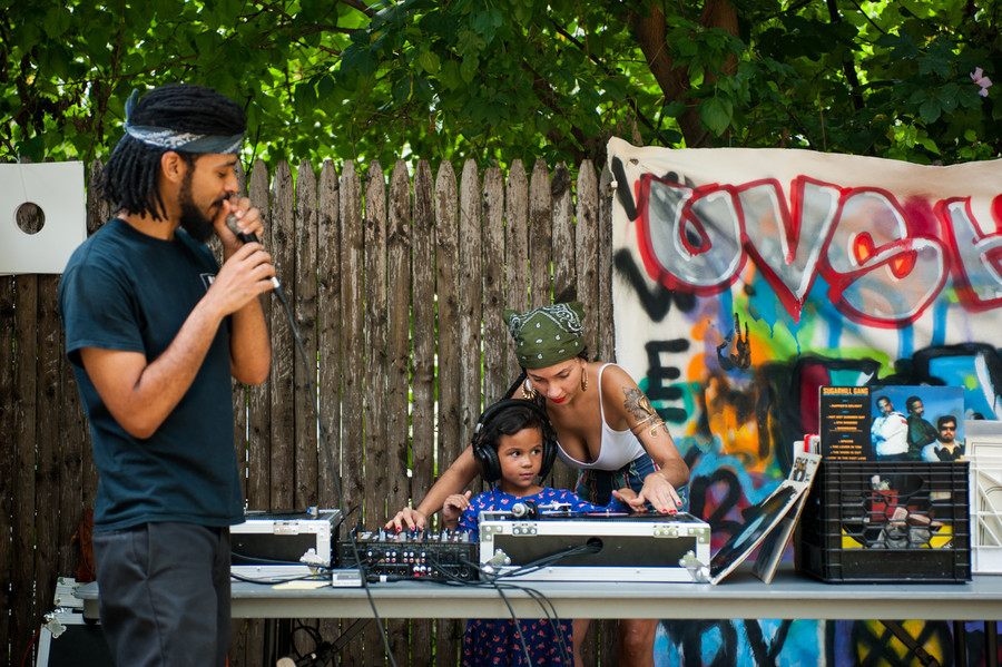 Sunny Vazquez helps party guest Scarlett Gomez scratch a record at the summer jam.