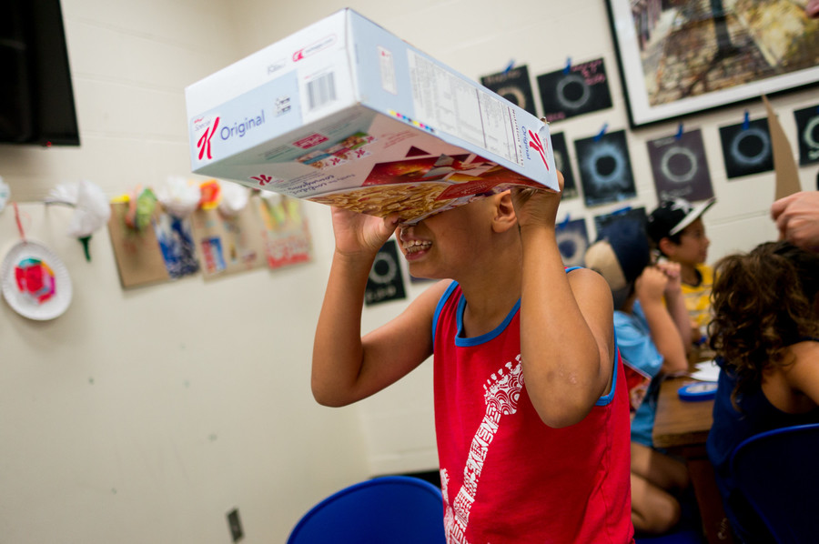 An earnest young astronomer tests out his makeshift pinhole box ahead of the solar eclipse.