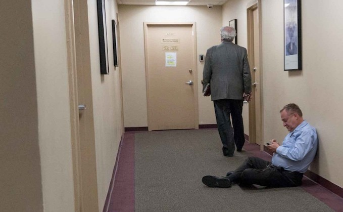 Michael Heller sits on the floor in front of Riverdale Mental Health Association's offices in April as an executive committee meeting debated he and three other finalists for Community Board 8's district manager position.