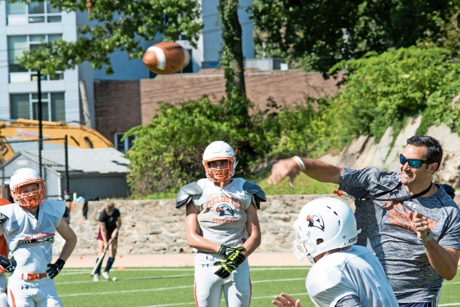 Fieldston head football coach Gus Ornstein, who knows a thing or two about playing quarterback from his days at Notre Dame and Michigan State, shows his players how it's done at a recent practice as the Eagles prepare for their Sept. 9 season opener.
