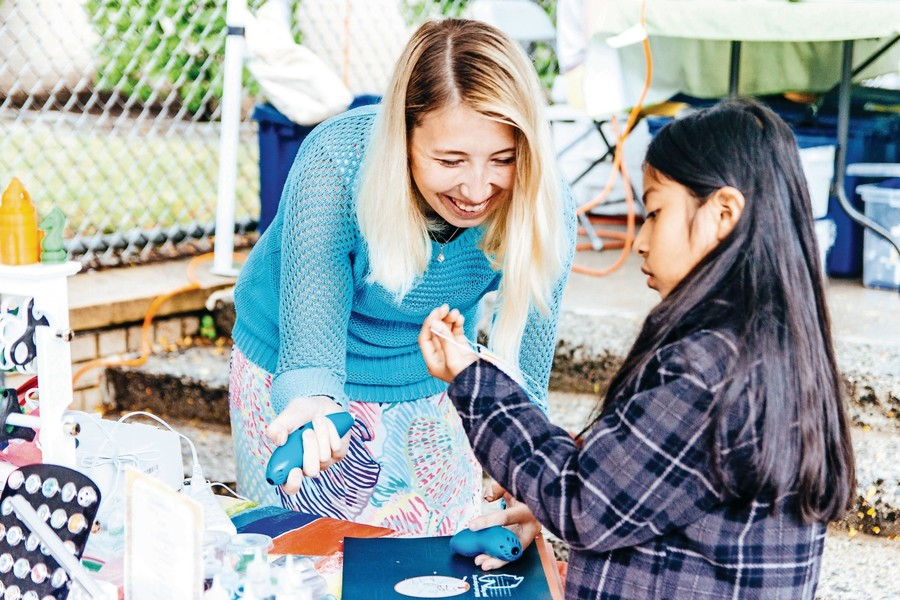 Erika Gillette, a visiting professor at the College of Mount Saint Vincent, helps a young girl,  Dana, make a 3-D-printed creation at The Riverdale Y's Sunday Market.