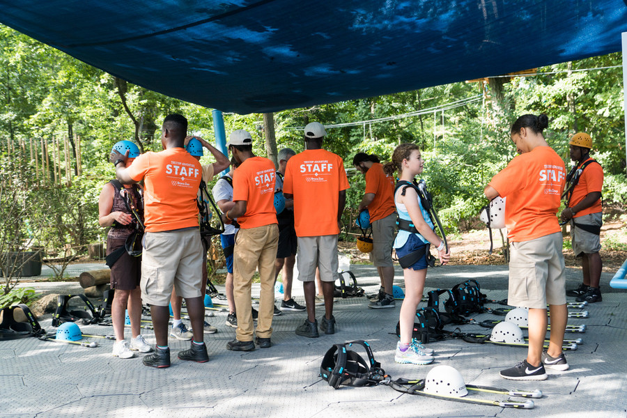 Staff members with the Bronx Zoo's Treetop Adventure help new explorers put on their safety gear.