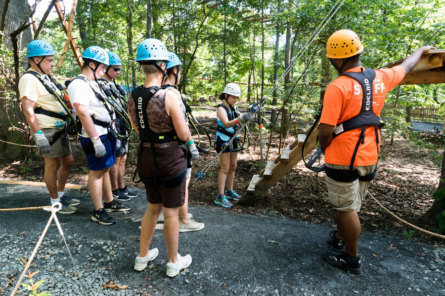 Emma Gelman, center, gets ready to go through the practice course at the Bronx Zoo's treetop adventure.