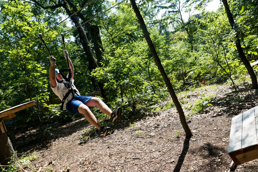 Declan O'Ferrall glides down the practice zip line in the Bronx Zoo's Treetop Adventure.