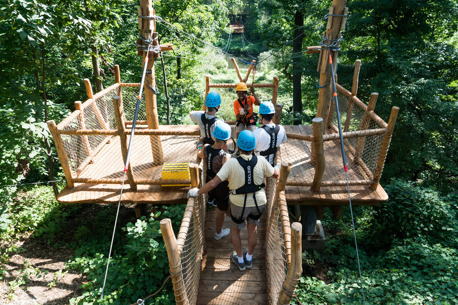Kakra Conduah, a ranger with the Bronx Zoo's Treetop Adventure, explains the zip line to the O'Ferrall family.