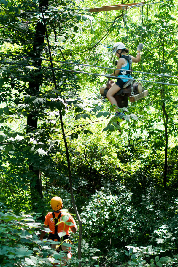 Emma Gelman slides down the zip line on a horseback saddle in the Bronx Zoo's Treetop Adventure.