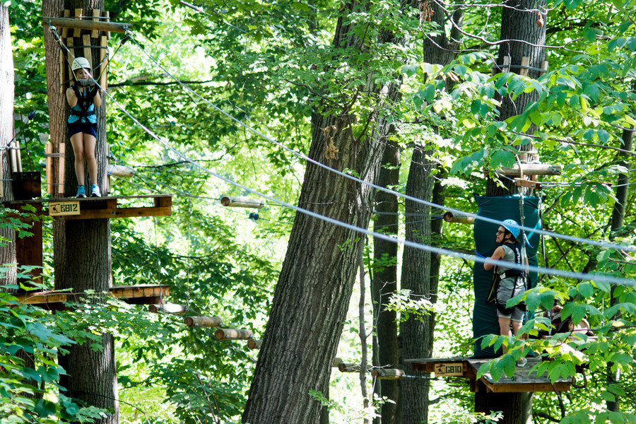 Inga Reznik, right, watches her daughter Emma prepare to slide down the final zip ine.