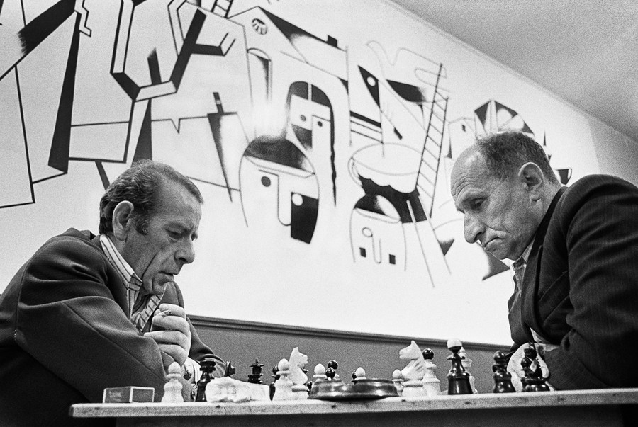 Two men engage in a chess game at the Jewish Club in Lodz, Poland, in 1975. Photographer Chuck Fishman captured this image at a time when approximately 500 Jews remained in the area and some frequented the club.