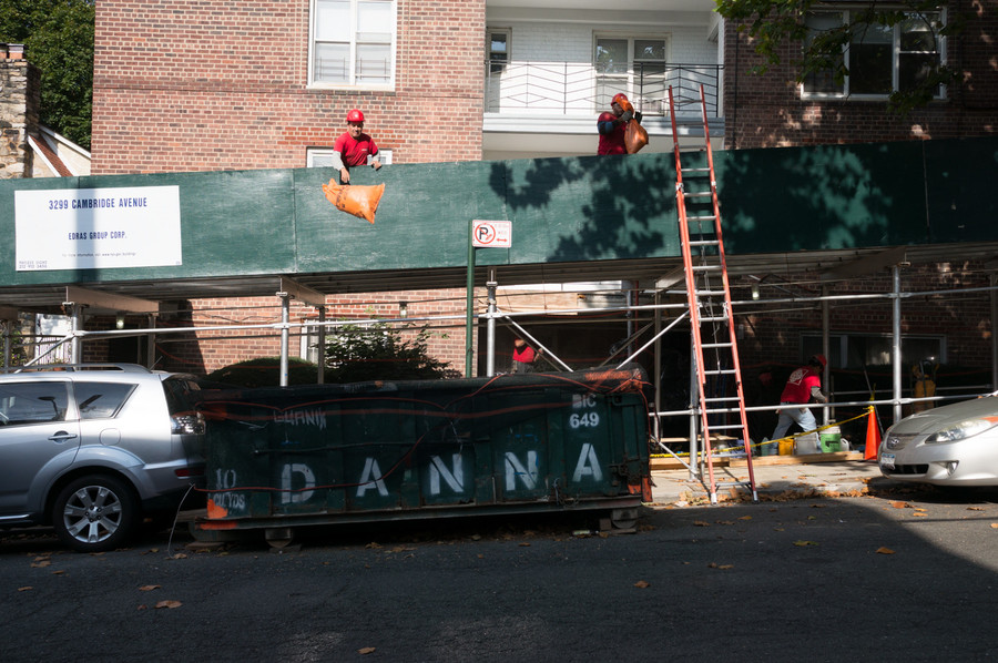 Construction workers atop scaffolding toss garbage into a dumpster.