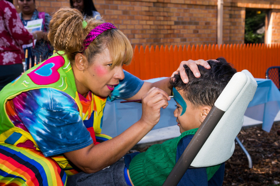 Maria Lopez paints a child's face at the opening ceremony.