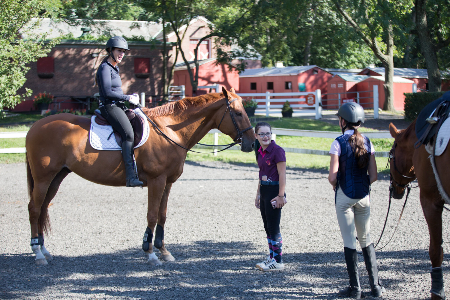 Samantha Goldberg, left, talks with fellow rider Sloane Mayman at the Riverdale Stables. The two are some of the many riders the stable accommodates throughout the year.