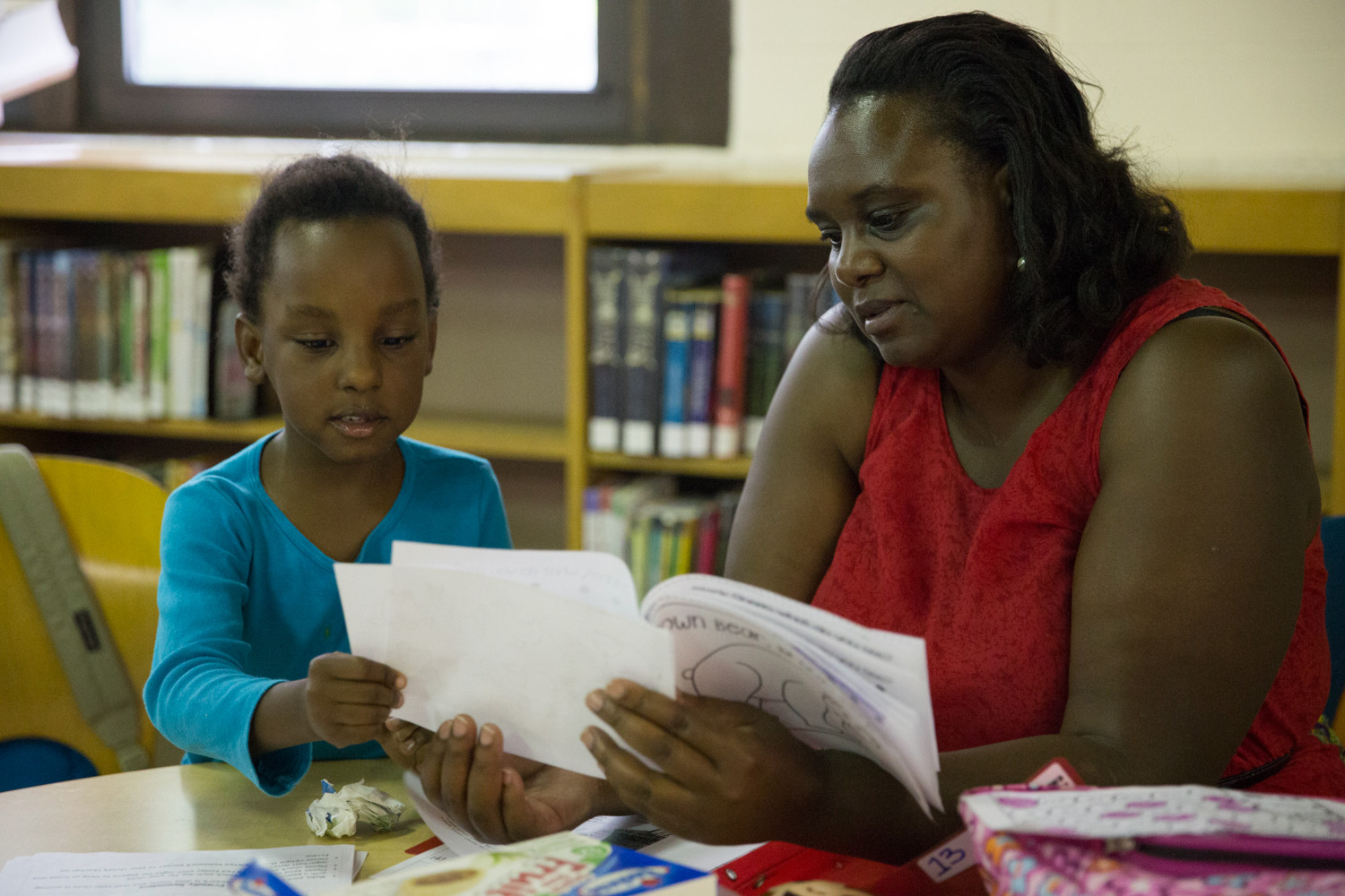 Monica Muraguri reads with her daughter Hashabiah Ndegwa . All three of her children use the branch's tutoring service.