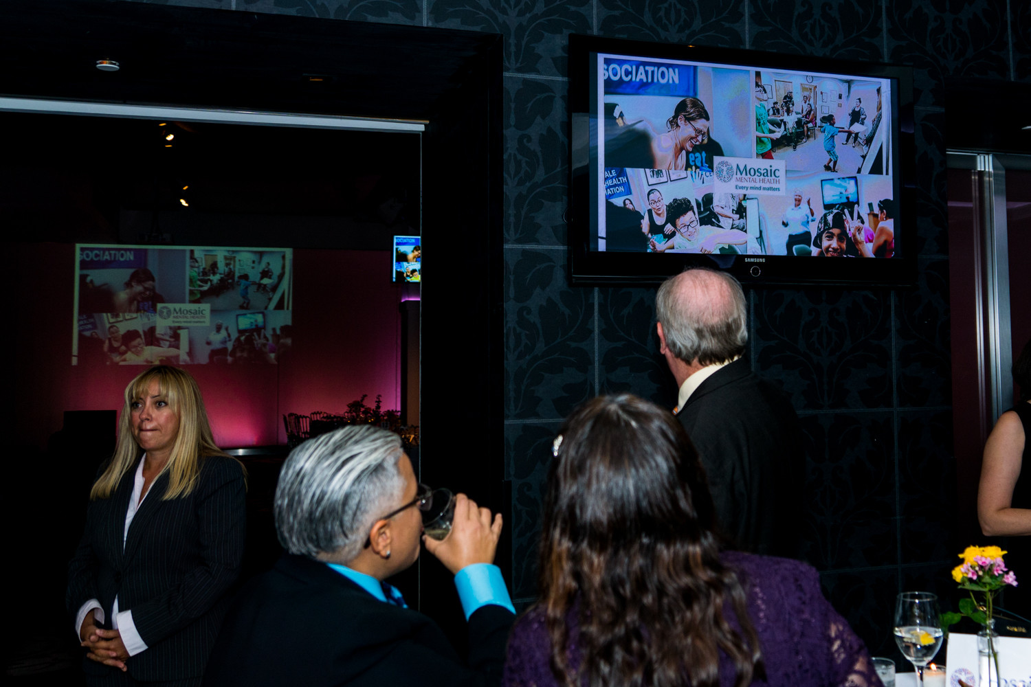 Gala attendees look at a slideshow about Mosaic Mental Health. The organization offers services like counseling and youth programs, serving 1,000 patients annually.