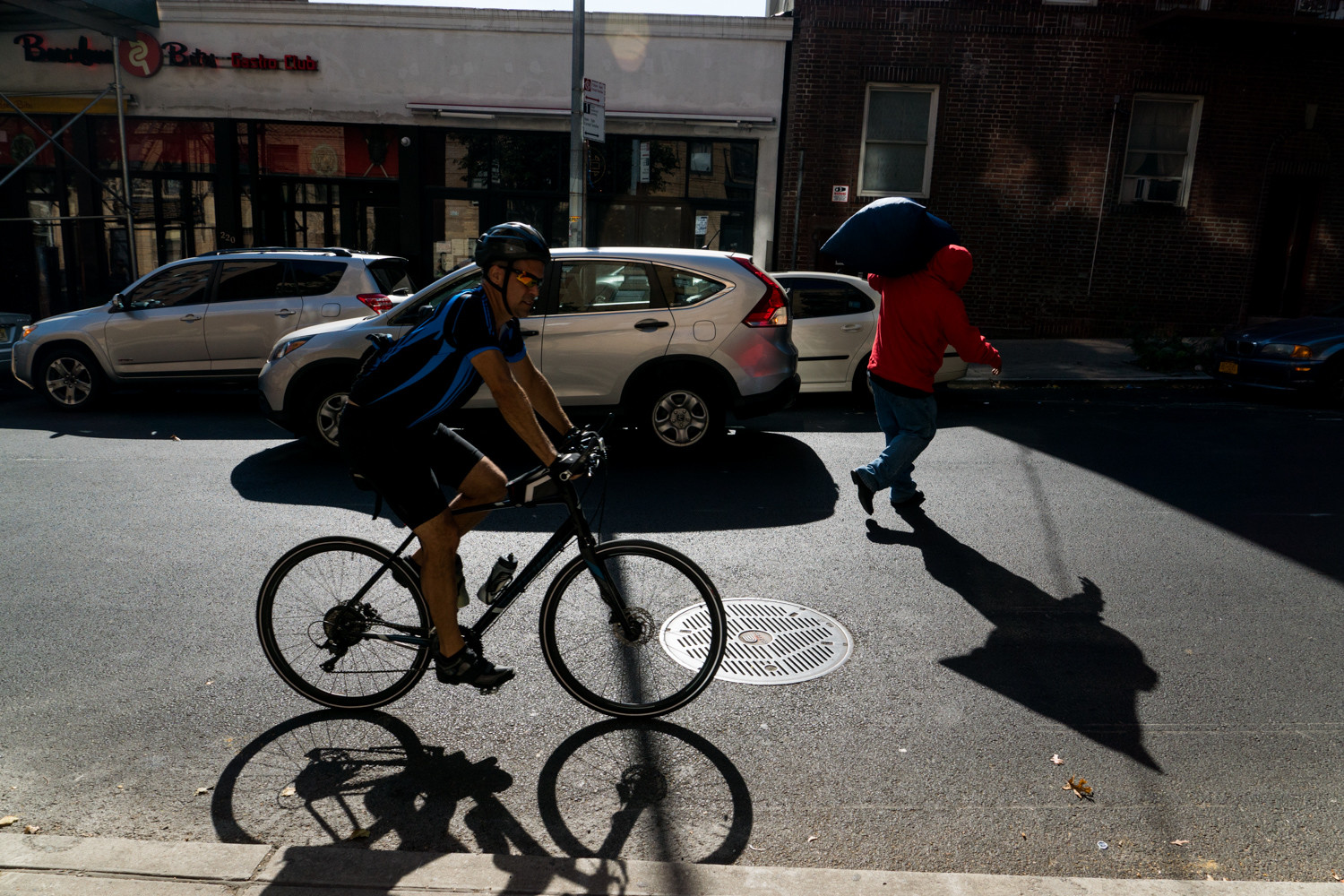 A cyclist pushes up West 242nd Street towards Manhattan College Parkway as a Bronxite carries his laundry.