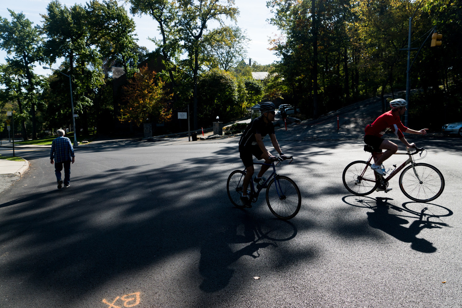 Cyclists cross paths with a pedestrian along Manhattan College Parkway in the Tour de Bronx.