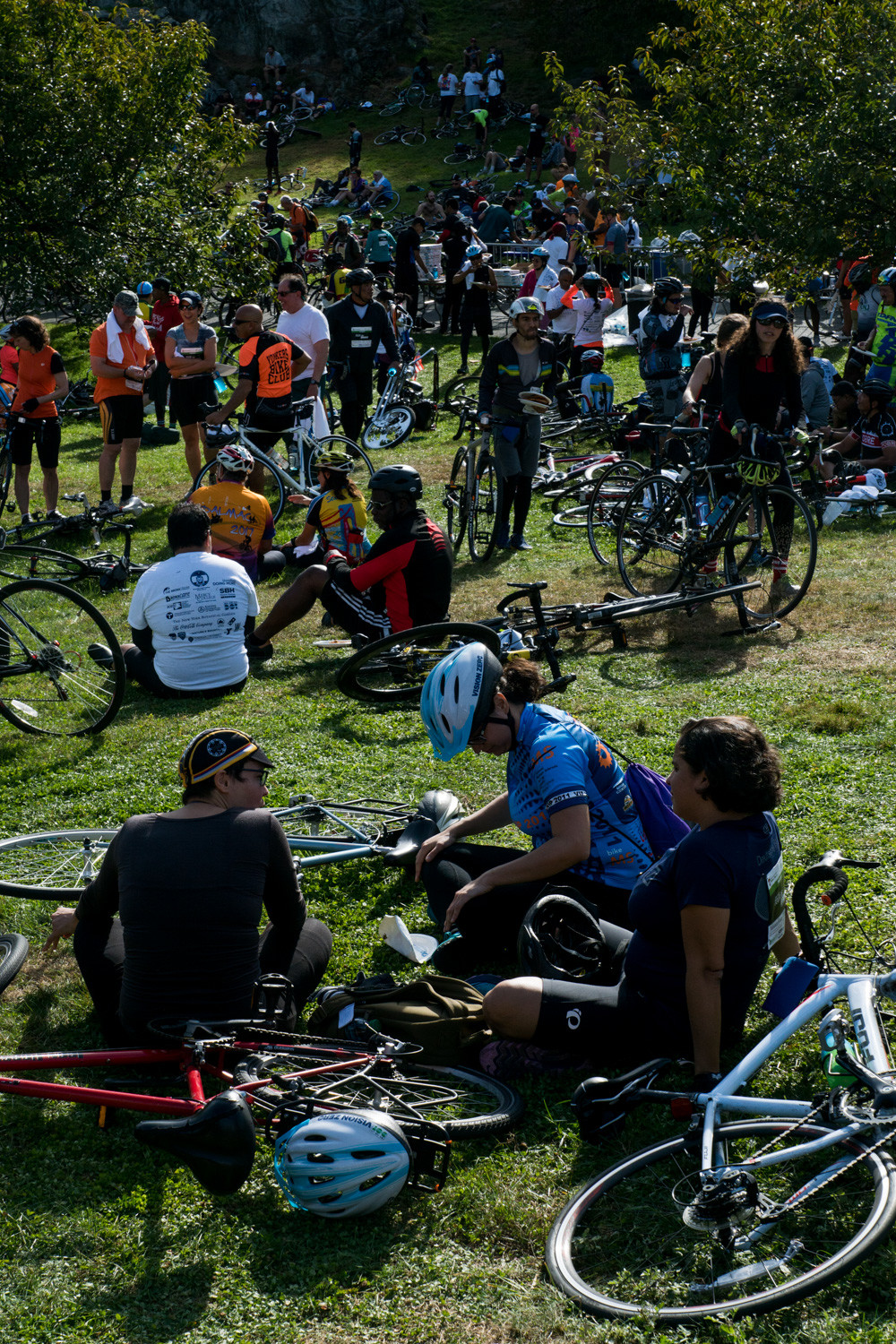 Cyclists rest on the grass in the New York Botanical Garden at the end of the Tour de Bronx.