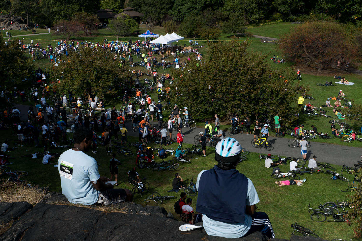 Cyclists sit on a rock overlooking the New York Botanical Garden at the end of the Tour de Bronx.
