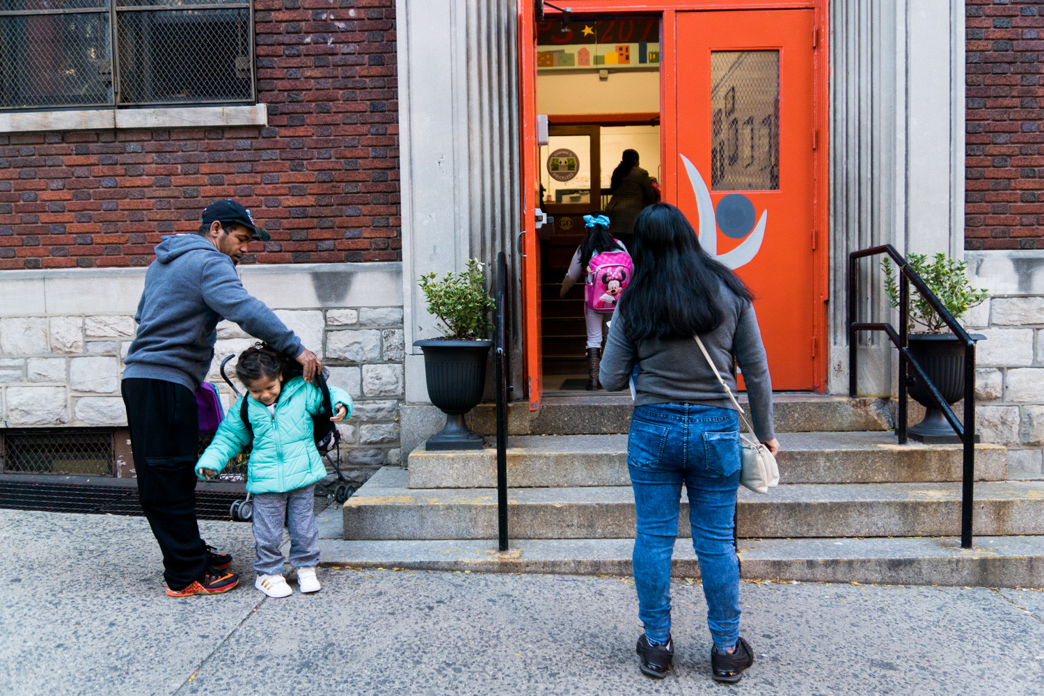 Parents drop off their children at the start of the school day at P.S. 207, which serves kindergarten through second grade. There is a proposal to expand P.S. 207 so students could remain at the school through fifth grade.