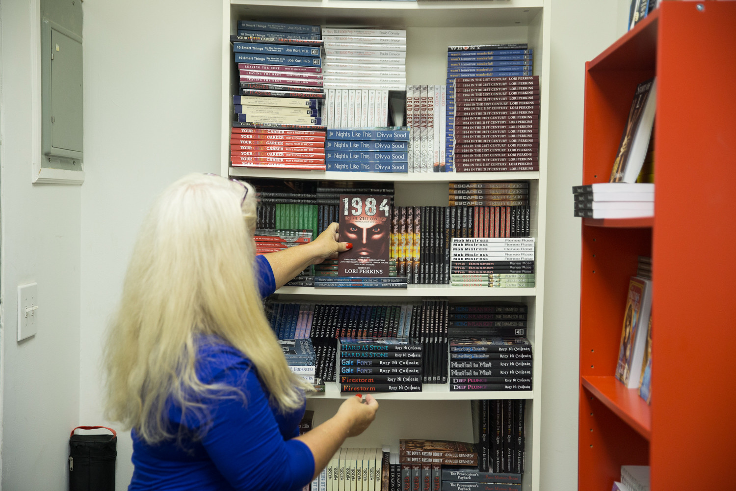 Perkins peruses a bookshelf in the Riverdale Avenue Books office. Perkins is publishing a collection of essays in response to the Harvey Weinstein controversy. The book includes stories from people who have been victims of sexual harassment and assault.