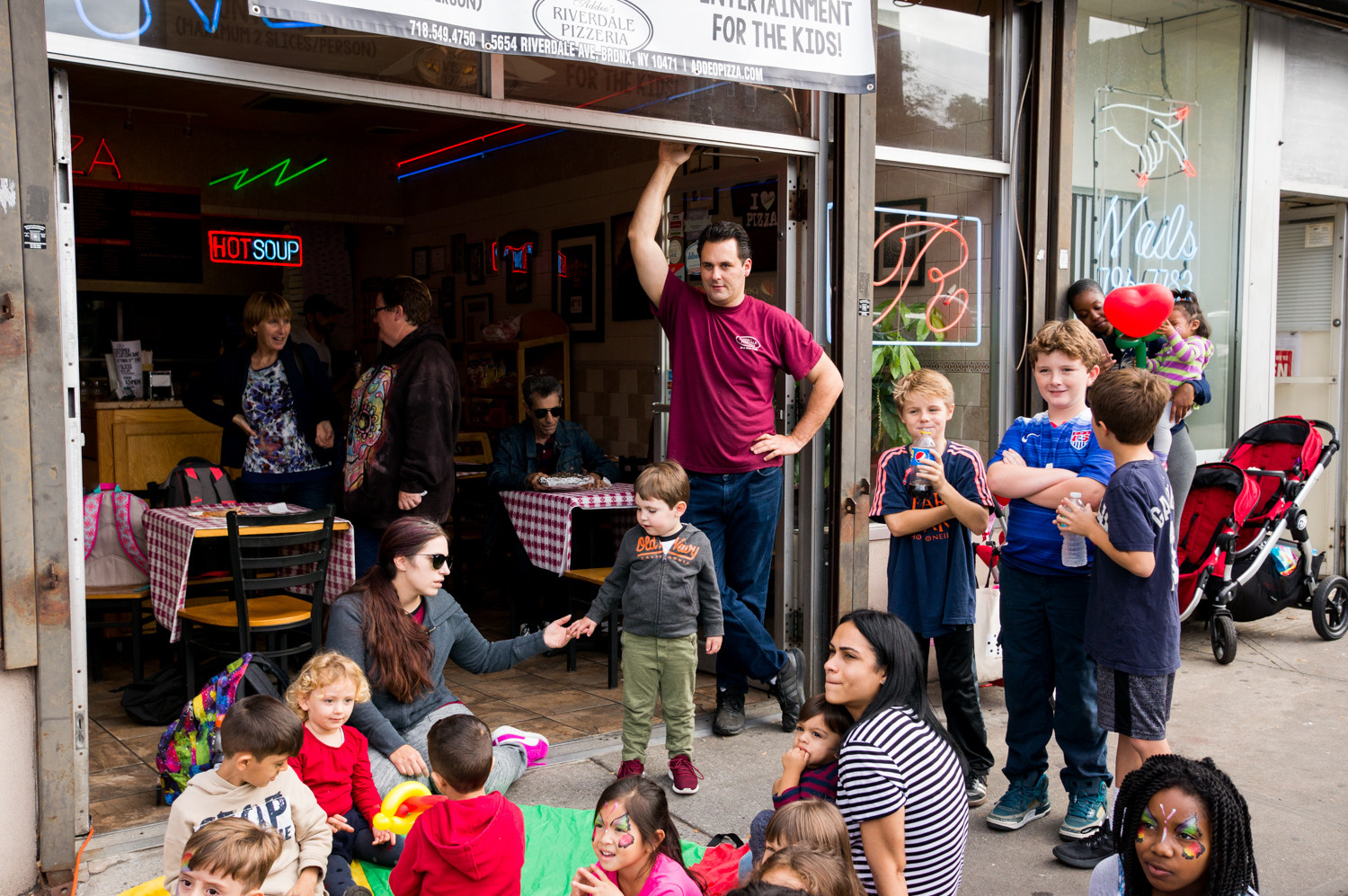 Laurence Addeo, owner of Addeo's Riverdale Pizza, watches as the clowns entertain the kids for his customer appreciation day, which also had pizza slices on sale for $1 each.