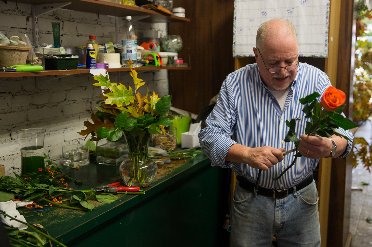 John McKeon, owner of John's Botany Bay Florist, removes leaves and thorns from a rose in the back of his Riverdale Avenue shop. Originally from Washington Heights, McKeon has worked at the shop for 25 years, owning it for the last 20.
