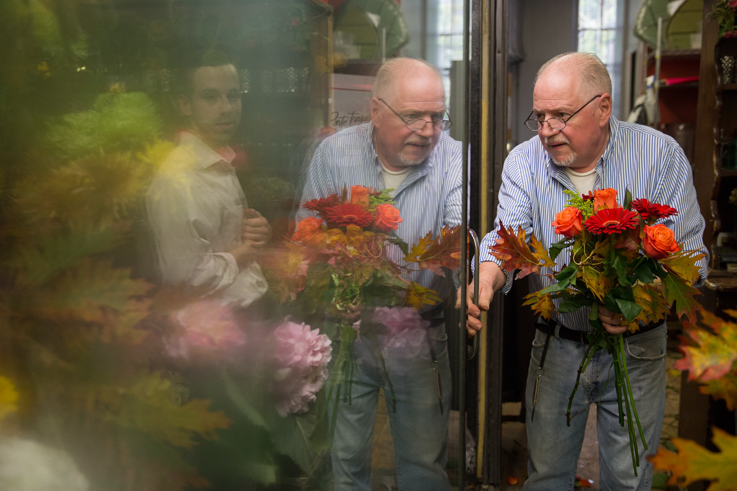 John McKeon, owner of John's Botany Bay Florist, prepares a bouquet while a customer assesses the assortment. The shop was humming on a recent afternoon as McKeon hustled to keep up with a flood of end-of-day orders.