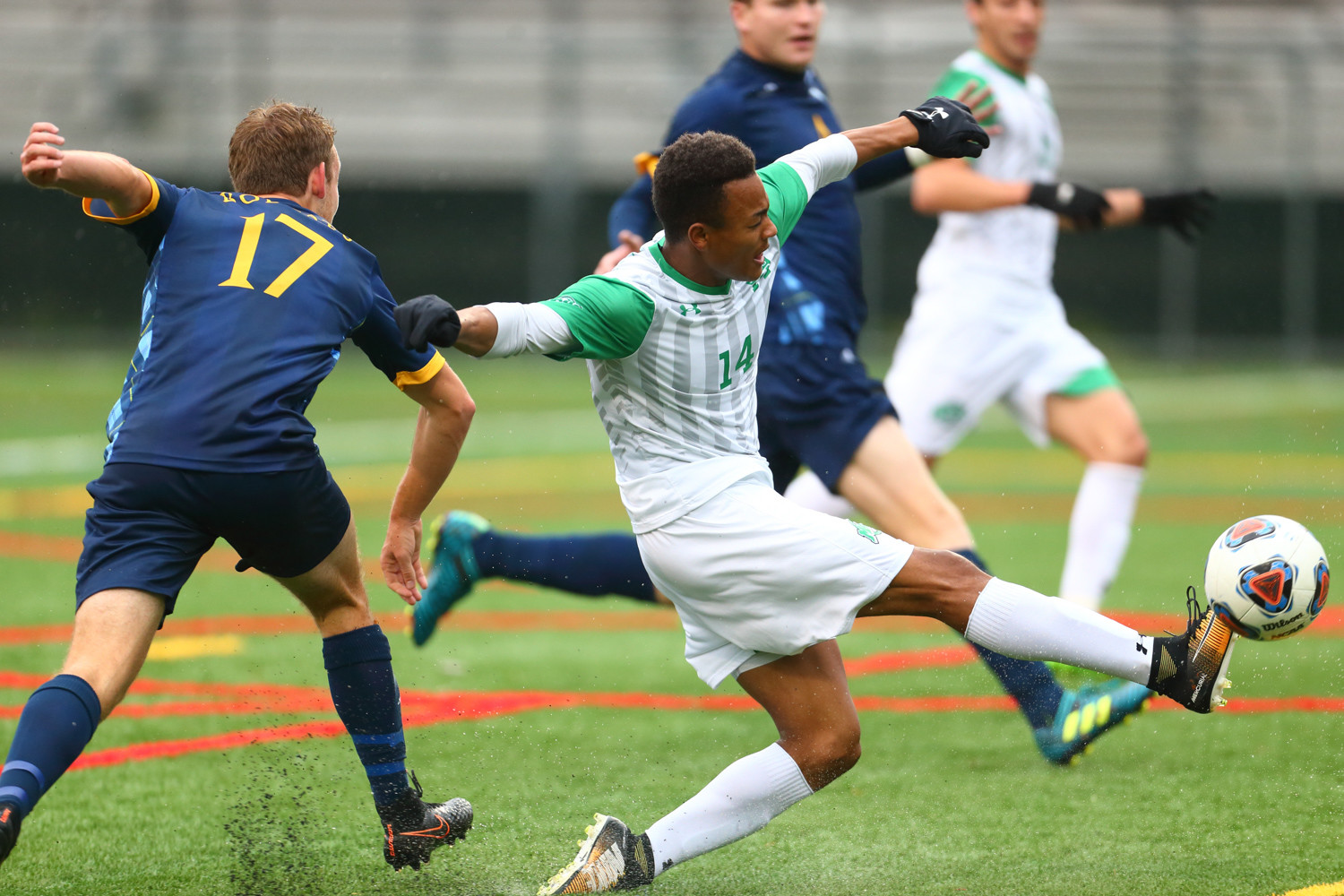 Manhattan's Troy Carrington (14) works his way around a couple of Quinnipiac defenders in the Jaspers' MAAC Tournament quarterfinal game at Gaelic Park.