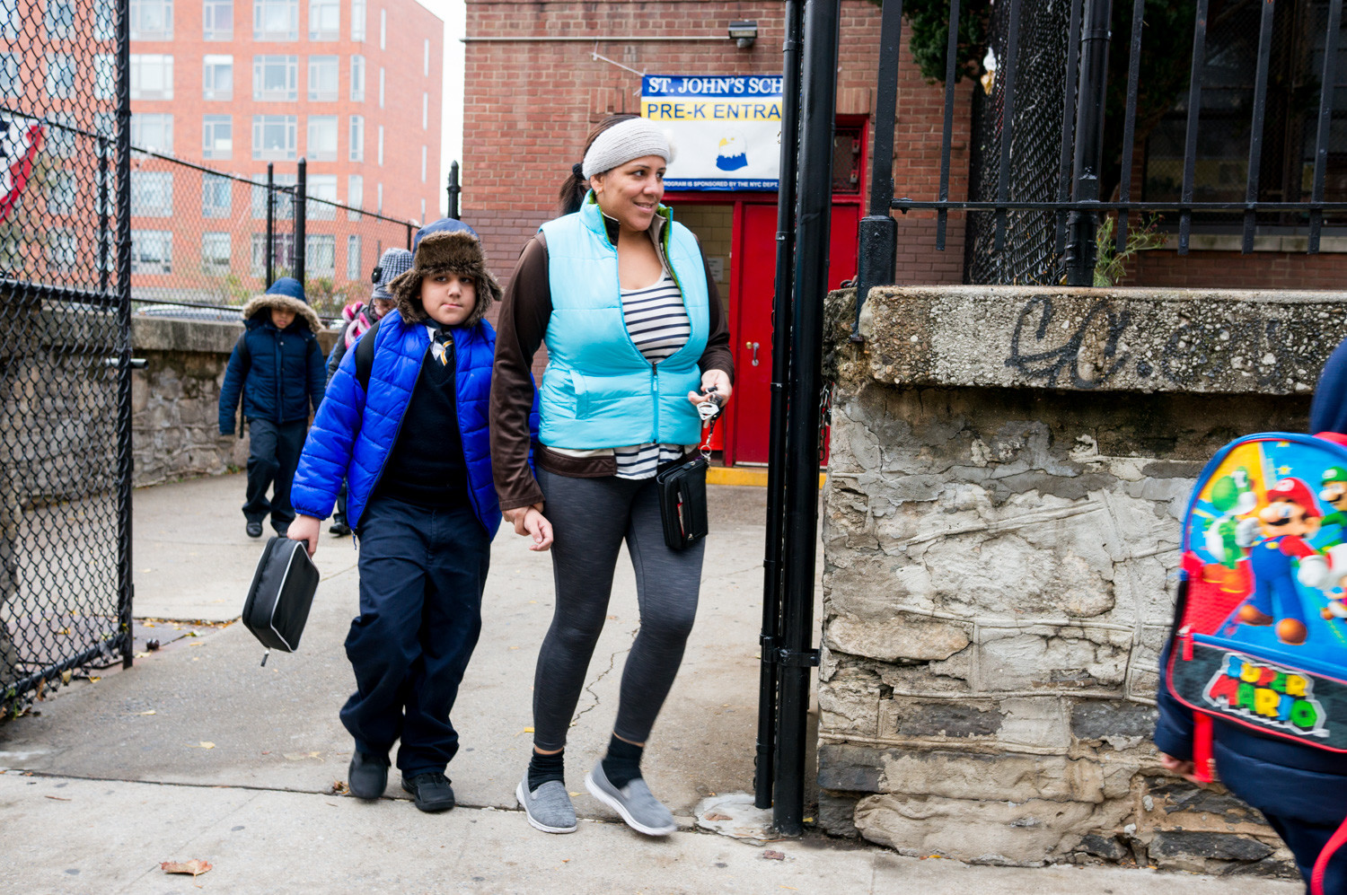 Parents pick up their children from St. John's School in Kingsbridge. After the former principal's surprise departure, the Archdiocese of New York appointed Melissa Cardona-Moore to manage the school. Her leadership has come under scrutiny by at least one parent demanding answers as to why her son was seen walking alone outside the school..
