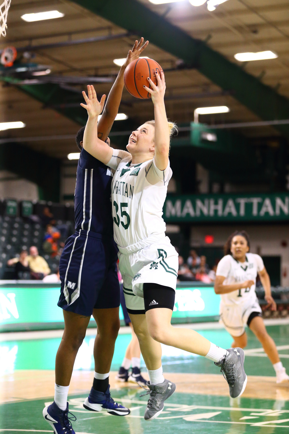 Manhattan's Kayla Grimme (35) battles against Monmouth last season, and is back for her senior year this winter after leading the Jaspers in both scoring and rebounding last season.