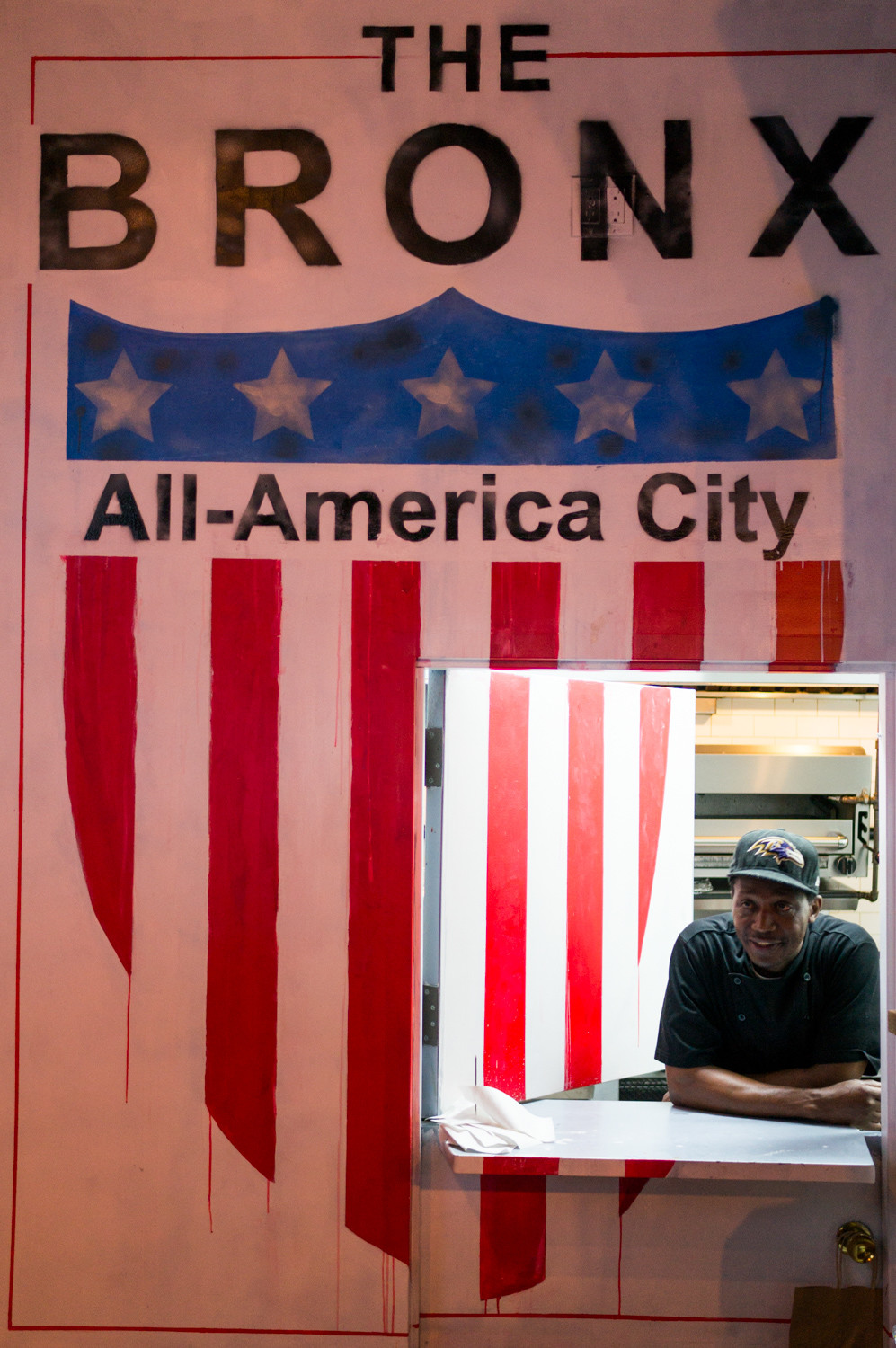 A cook rests his arms at the handoff window in The Bronx Public, who plays a vital role for the Bronx Public's team.