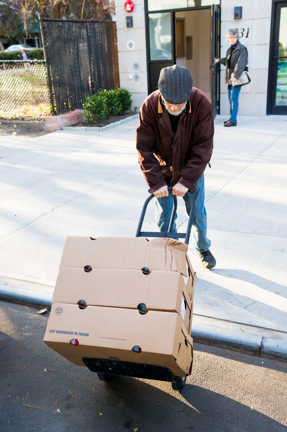 Ivan Braun, a member of Welcoming Neighbors Northwest Bronx, heaves a hand truck stacked with turkeys onto the sidewalk. The group raised nearly $2,500 to purchase Thanksgiving meals for families living in the transitional housing facility at 5731 Broadway.