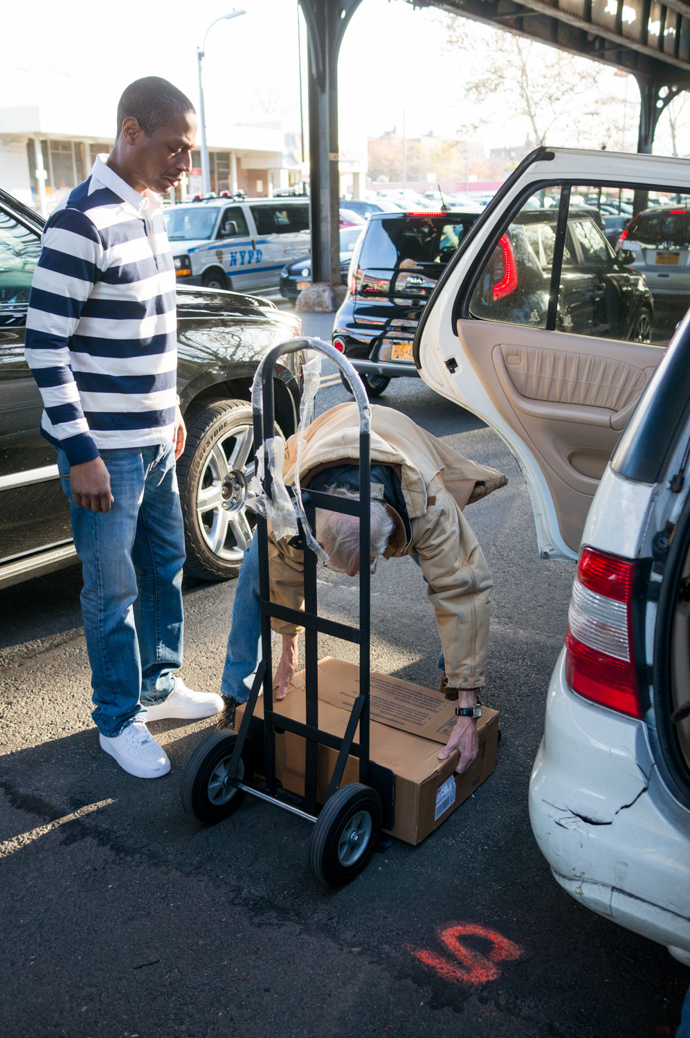 Bill Lewis, a member of Welcoming Neighbors Northwest Bronx, places a box of turkeys on a hand truck. The group raised nearly $2,500 to purchase Thanksgiving meals for families living in the transitional housing facility at 5731 Broadway.