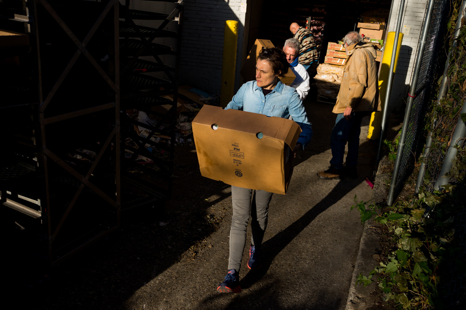 Kate Sann, a member of Welcoming Neighbors Northwest Bronx, carries a box of turkeys to a waiting car.