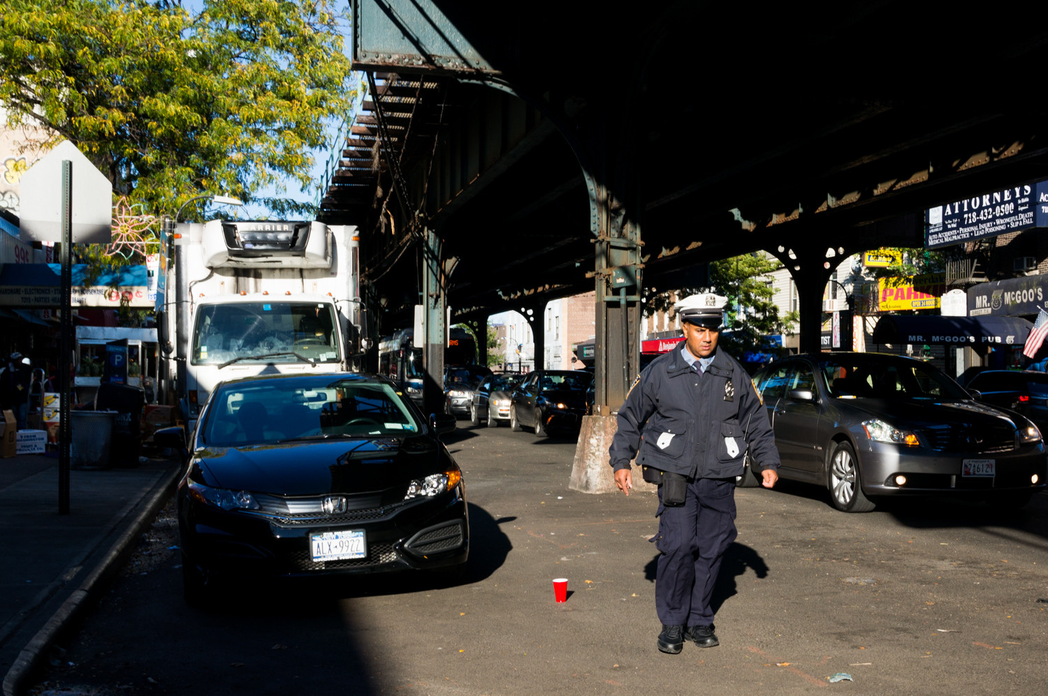 A traffic cop walks along Broadway looking for parking violators. Several recent high-profile incidents in the Bronx, including a viral video of a cop punching a 16-year-old alleged bicycle thief, have strained police-community relations.