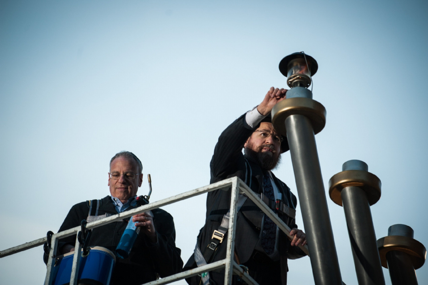 Standing with Assemblyman Jeffrey Dinowitz, Rabbi Levi Shemtov lights the menorah last year to help kick off annual Hanukkah celebrations. The lighting this year takes place Dec. 17 at 4 p.m., at the Riverdale Monument.