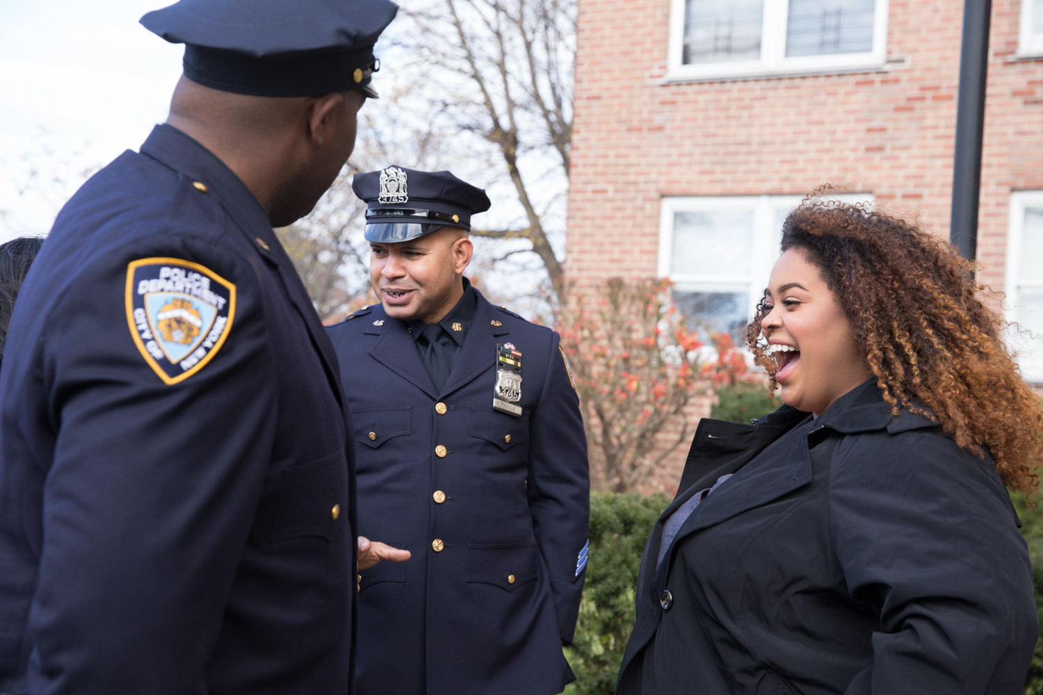 Genesis Villella, the eldest daughter of slain police officer Miosotis Familia, laughs with members of the New York Police Department after a news conference announcing her family's new home at Skyview-on-the-Hudson.