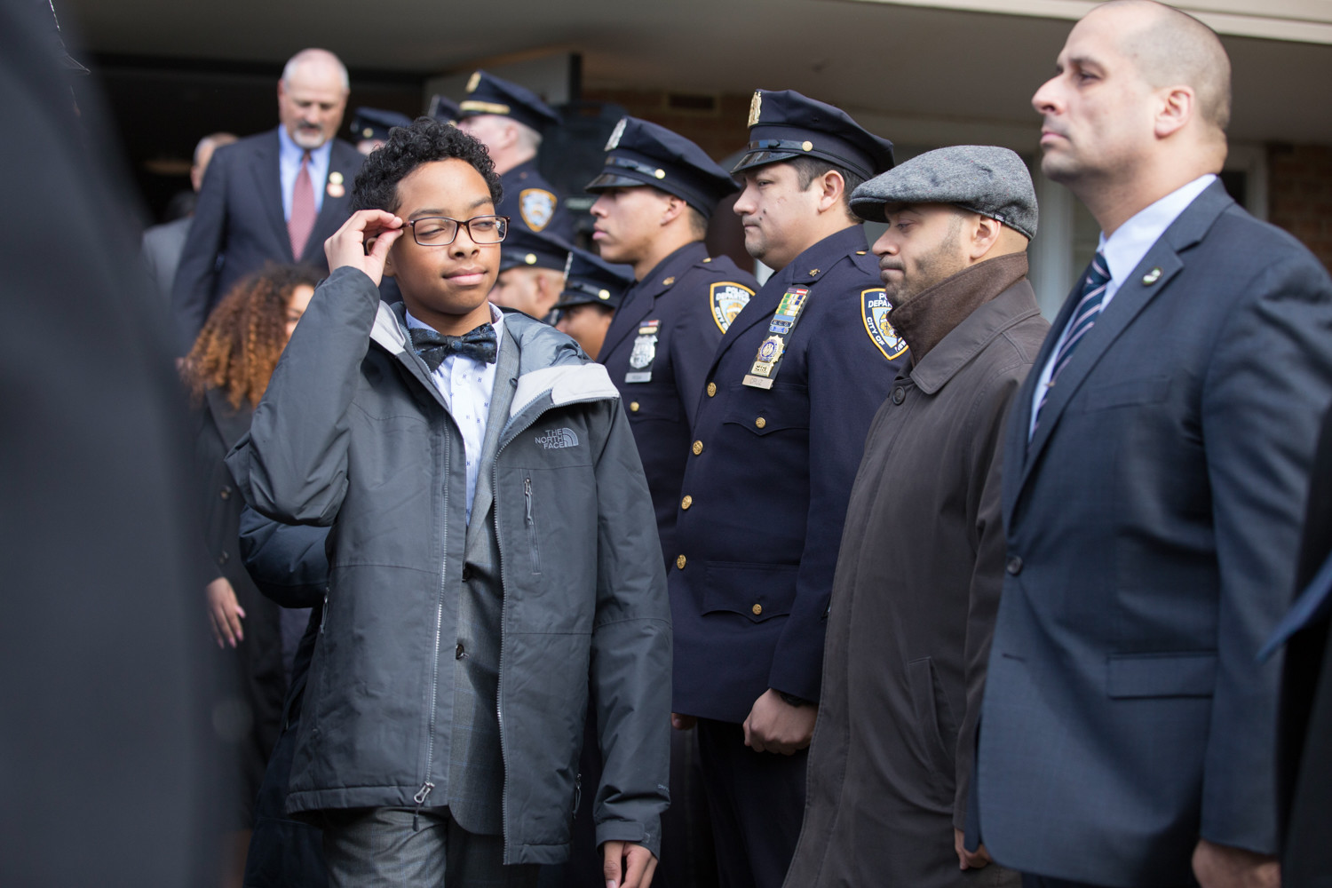 New York Police Department officers stand at attention as Peter Vega, son of the late Miosotis Familia, leaves a news conference where he and his sisters were given a home at Skyview-on-the-Hudson.