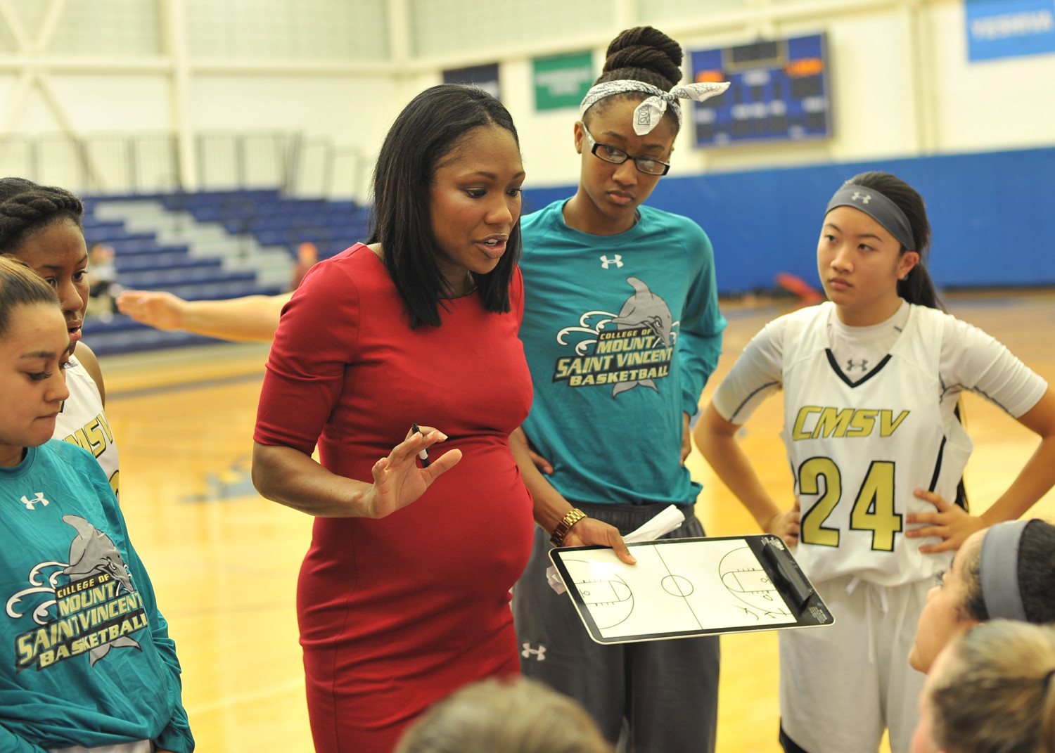 New Mount Saint Vincent women's head basketball coach Tiffany Smart discusses strategy with her Dolphins as she notched a win in her first home game of the season.