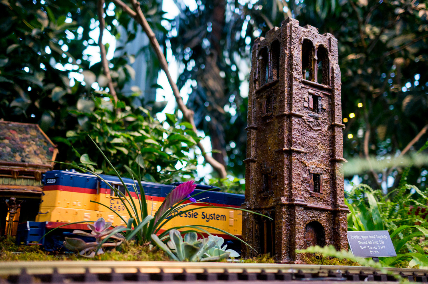 A model train passes by a replica of the Riverdale Monument at the New York Botanical Garden's Holiday Train Show. The show is an annual tradition that brings together the work of the company Applied Imagination, whose artists and technicians create replicas of famous New York buildings, statues and structures from natural materials.
