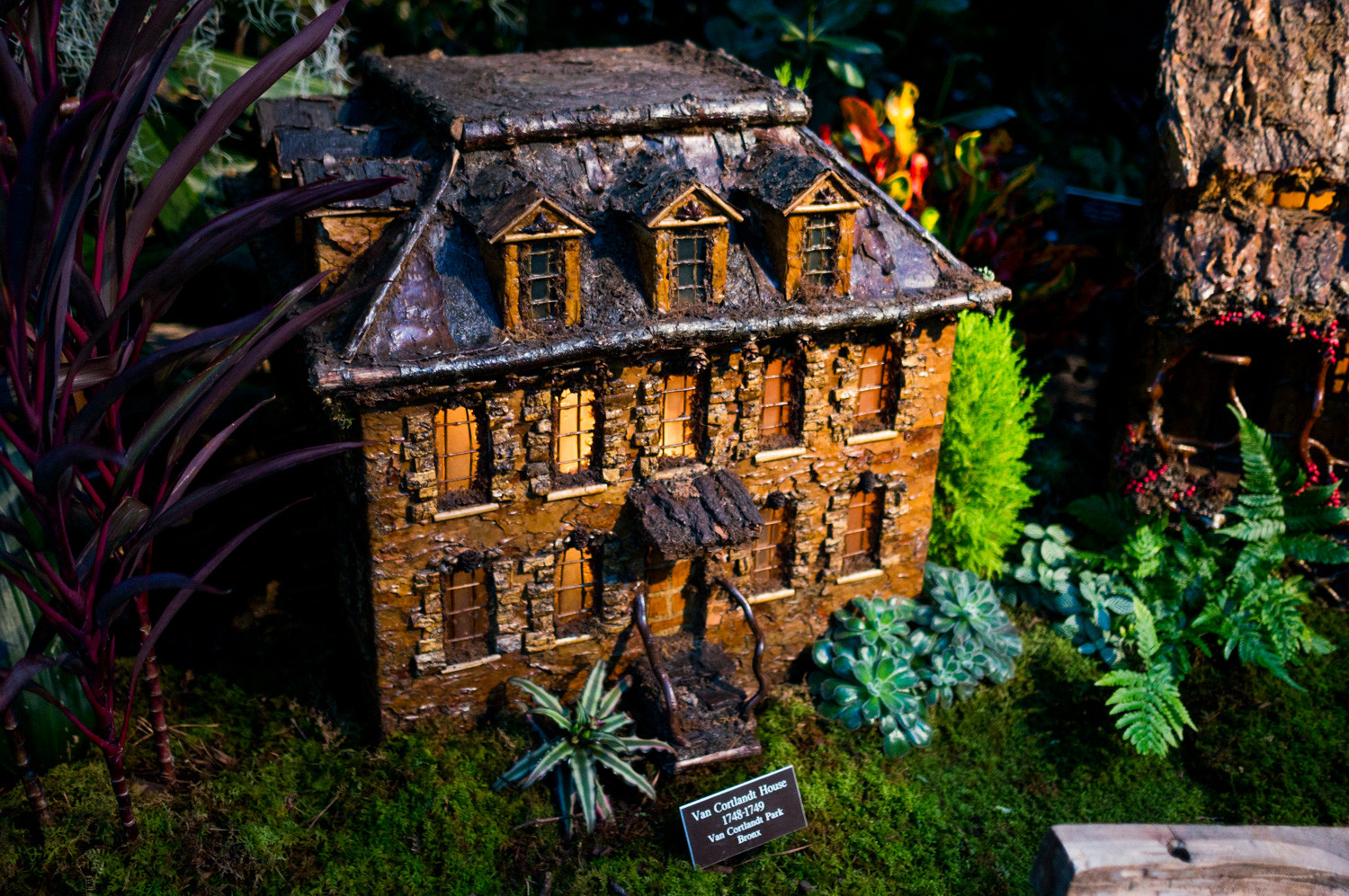 A replica of the Van Cortlandt House rests below a railway in the Holiday Train Show at the New York Botanical Garden. Built in 1748 and located just off the park that bears the same family name, the Van Cortlandt House is one of the oldest buildings in the Bronx.