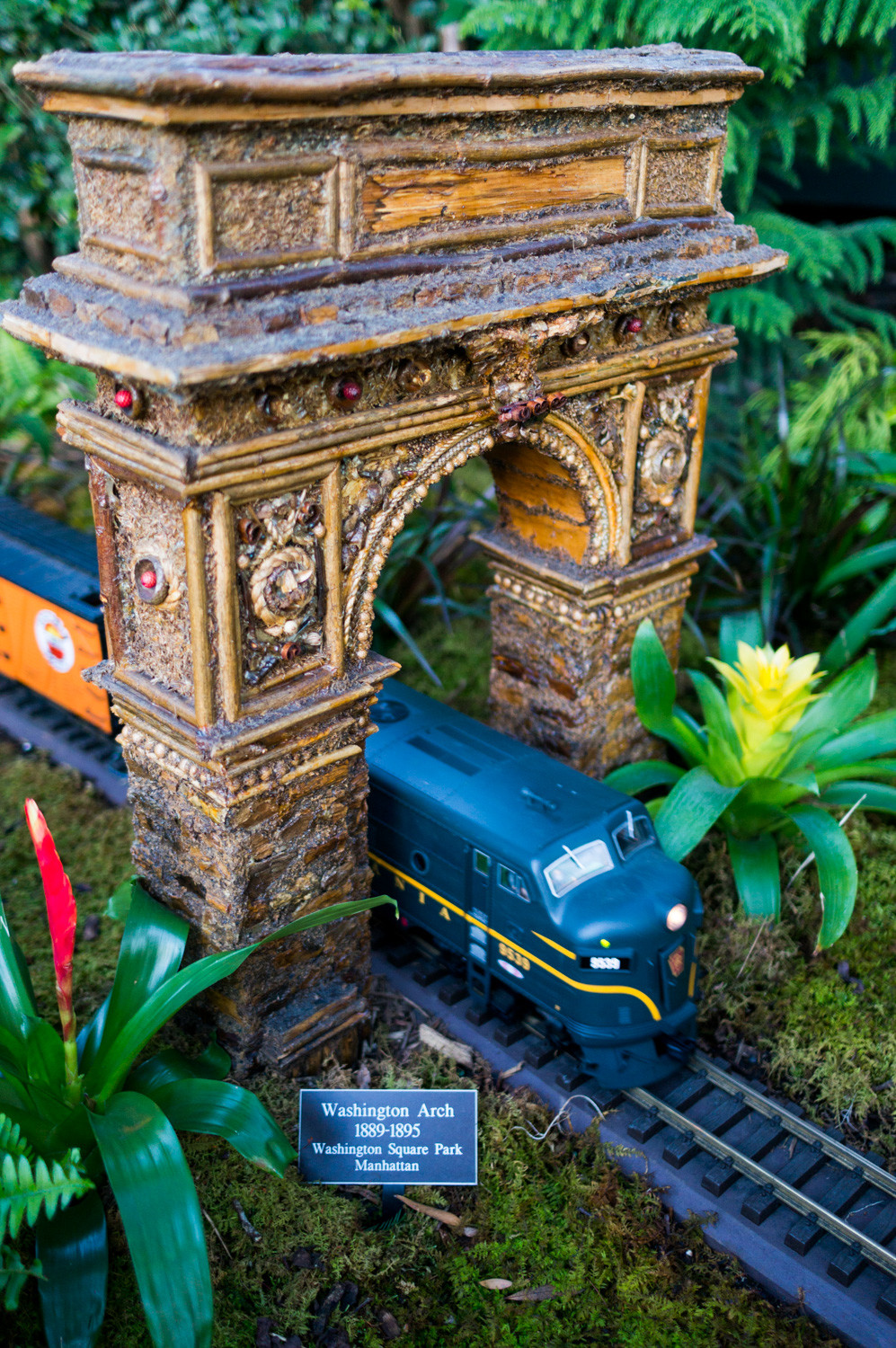 A model train passes under a replica of the Washington Arch in the Holiday Train Show at the New York Botanical Garden. The team of artists and technicians at Applied Imagination laid over a half-mile of train tracks in this year's show.