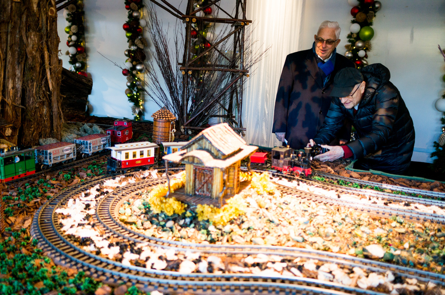 Patrons wait for the opportune moment to take a picture of a train in the first room of the Holiday Train Show at the New York Botanical Garden.